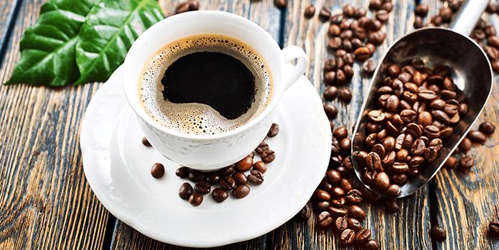 Xícara de café cercada de grãos; vivemos a terceira onda do café atualmente