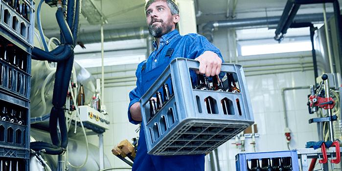Homem carrega caixa de cerveja